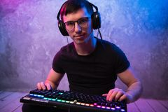 Retrato do pro gamer considerável novo que senta-se no assoalho com o teclado na sala colorida de néon imagem de stock