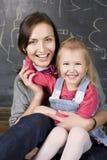 Retrato do professor e estudante, mãe e filha pequenos perto do quadro-negro Foto de Stock Royalty Free