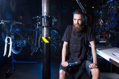 Retrato do proprietário empresarial pequeno do homem novo com barba Trabalhador da oficina do mecânico da bicicleta do indivíduo  foto de stock