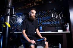 Retrato do proprietário empresarial pequeno do homem novo com barba Trabalhador da oficina do mecânico da bicicleta do indivíduo  fotos de stock