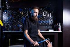 Retrato do proprietário empresarial pequeno do homem novo com barba Trabalhador da oficina do mecânico da bicicleta do indivíduo  imagens de stock