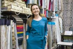 Retrato do proprietário maduro feliz da mulher na loja interior das telas, amostras da tela do fundo Loja de matéria têxtil da ca imagem de stock