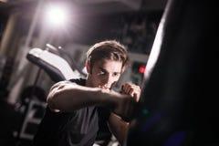 Retrato do pugilista que tenta a retroceder o saco de perfuração no gym ao treinar Treinamento Imagens de Stock Royalty Free