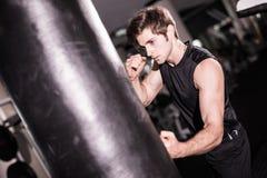 Retrato do pugilista que tenta a retroceder o saco de perfuração no gym ao treinar Treinamento Fotos de Stock