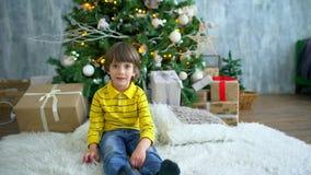 Retrato do rapaz pequeno alegre feliz bonito na manhã de Natal no interior home com decorações e abeto do feriado filme