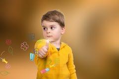 Retrato do rapaz pequeno bonito que dá lhe os polegares acima com as flores no fundo imagens de stock royalty free