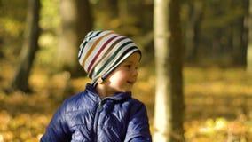 Retrato do rapaz pequeno bonito que gira e que gira no lugar Movimento lento vídeos de arquivo