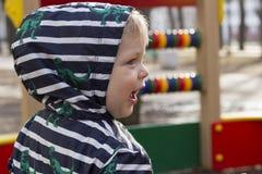 Retrato do rapaz pequeno de sorriso que joga fora no campo de jogos, menino da tampa em uma capa que joga fora Fotografia de Stock Royalty Free