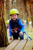 Retrato do rapaz pequeno feliz que tem o divertimento no parque da aventura que sorri ao capacete da câmera e ao equipamento de s foto de stock