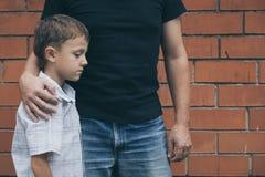 Retrato do rapaz pequeno novo e do pai tristes que sentam-se fora em Fotos de Stock
