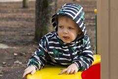 Retrato do rapaz pequeno pensativo que joga fora no campo de jogos, criança adorável em uma capa que joga fora Fotos de Stock Royalty Free