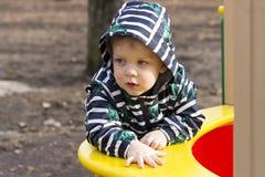 Retrato do rapaz pequeno pensativo que joga fora no campo de jogos, criança adorável em uma capa que joga fora Foto de Stock