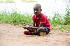 Retrato do rapaz pequeno que senta-se apenas no coração da natureza imagens de stock