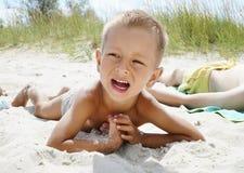 Retrato do rapaz pequeno que sorri no fundo da praia do mar imagens de stock