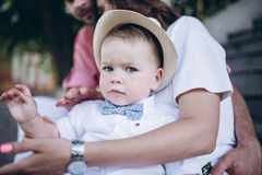 Retrato do rapaz pequeno Senta-se nas escadas com pais em seus joelhos do ` s da mãe Imagem com foco seletivo na criança Imagens de Stock Royalty Free