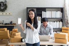 Retrato do smartphone asiático de sorriso da posse da jovem mulher com estar das caixas de cartão fotos de stock royalty free