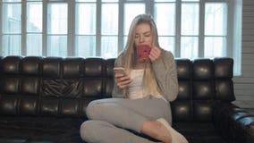 Retrato do smartphone vestindo da maçã da jovem mulher que senta-se no sofá Um louro bonito escreve sms sobre contra um grande filme