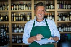 Retrato do sommelier que toma o inventário na loja de vinhos Imagens de Stock