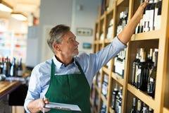Retrato do sommelier que toma o inventário na loja de vinhos Foto de Stock Royalty Free