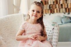 Retrato do sorriso bonito 5 anos de menina idosa da criança que senta-se na cadeira Imagens de Stock Royalty Free