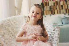 Retrato do sorriso bonito 5 anos de menina idosa da criança que senta-se na cadeira Foto de Stock