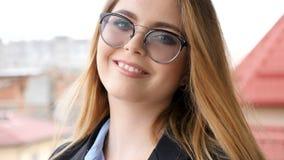 Retrato do sorriso louro bonito da mulher de negócios natural à câmera filme