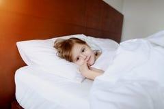 Retrato do sorriso pequeno da filha que coloca na casa branca da cama no bom dia ensolarado Imagens de Stock Royalty Free