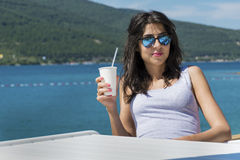 Retrato do suco bebendo da jovem mulher na praia Imagens de Stock