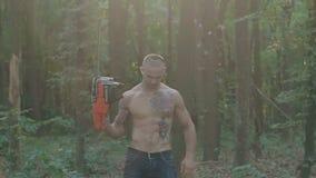 Retrato do suporte brutal do homem com serra de cadeia à disposição na floresta lentamente filme