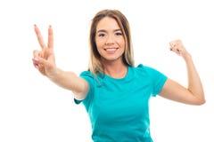 Retrato do t-shirt vestindo da menina bonita nova que mostra o ge da vitória fotografia de stock royalty free