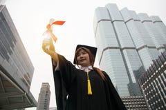 Retrato do tampão vestindo graduado bem sucedido do estudante fêmea e do g fotografia de stock royalty free