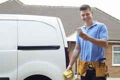 Retrato do telefone celular de Checking Message On do eletricista imagens de stock