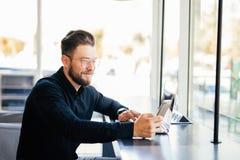 Retrato do telefone farpado novo do uso do homem de negócio no lugar de funcionamento no escritório moderno imagem de stock