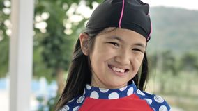 Retrato do terno de natação vestindo da menina asiática feliz que olha a câmera filme