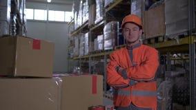 Retrato do trabalhador com as mãos dobradas em suportes da caixa no uniforme alaranjado brilhante perto de muitas caixas no armaz filme