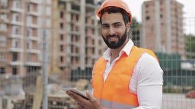 Retrato do trabalhador da construção no terreno de construção com a tabuleta que olha a câmera Profissões, construção, trabalhado video estoque
