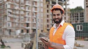 Retrato do trabalhador da construção no terreno de construção com a tabuleta que olha a câmera Profissões, construção, trabalhado vídeos de arquivo