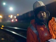Retrato do trabalhador da construção novo no capacete na noite fotografia de stock royalty free
