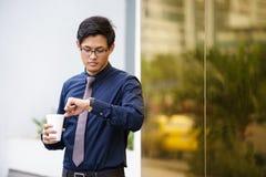 Retrato do trabalhador de escritório chinês que verifica o relógio do tempo Fotografia de Stock Royalty Free