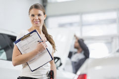 Retrato do trabalhador fêmea de sorriso do reparo com a prancheta na oficina do carro Foto de Stock Royalty Free