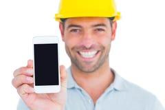 Retrato do trabalhador manual de sorriso que mostra o telefone esperto Fotos de Stock