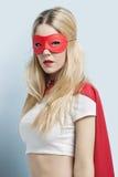 Retrato do traje vestindo do super-herói da jovem mulher contra o fundo azul fotos de stock royalty free