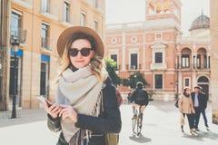 Retrato do turista de sorriso da mulher que está na rua da cidade contra o contexto da construção velha bonita, usando o smartpho Fotos de Stock