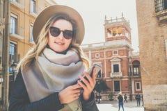 Retrato do turista de sorriso da mulher que está na rua da cidade contra o contexto da construção velha bonita, usando o smartpho Foto de Stock
