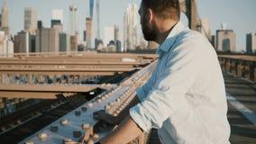 Retrato do turista feliz que inclina-se aos trilhos da ponte de Brooklyn, apreciando surpreendendo o panorama 4K da arquitetura d video estoque