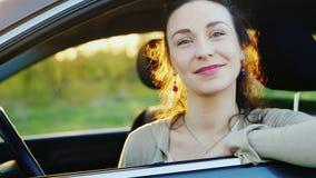Retrato do vídeo de movimento lento de um motorista fêmea novo Olha através da janela à câmera, sorrindo filme