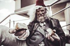 Retrato do vagabundo idoso que senta e que compartilha de seu bolo com o desconhecido imagens de stock royalty free