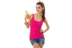 Retrato do verão da menina encantador nova na roupa leve com o cocktail no levantamento das mãos isolado no fundo branco Imagem de Stock