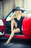 Retrato do verão da mulher loura à moda do vintage com os pés longos que levantam perto do carro retro vermelho fêmea justa atrat Foto de Stock Royalty Free