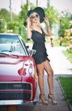 Retrato do verão da mulher loura à moda do vintage com os pés longos que levantam perto do carro retro vermelho fêmea justa atrat Imagens de Stock